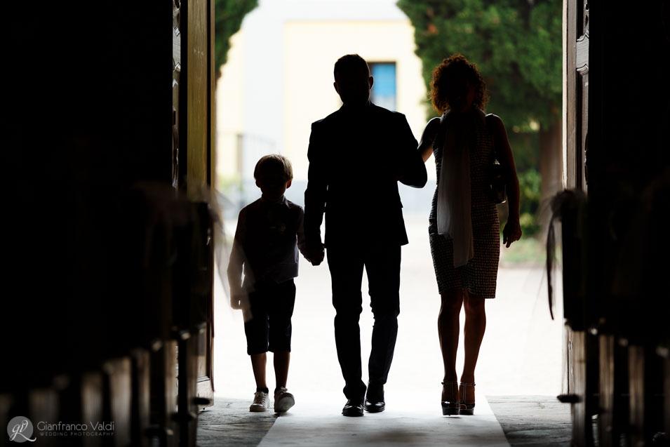 sposo entra in chiesa con mamma e figlio per celebrare le nozze