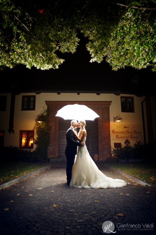sposi che si baciano sotto l'ombrello
