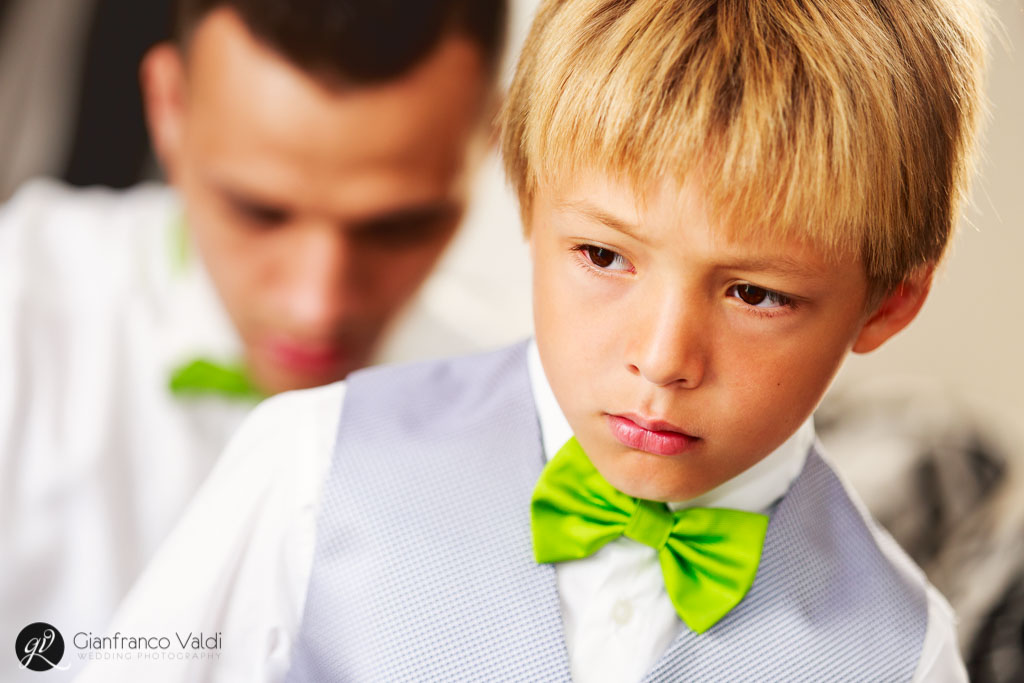 primo piano del bambino mentre il papà lo veste