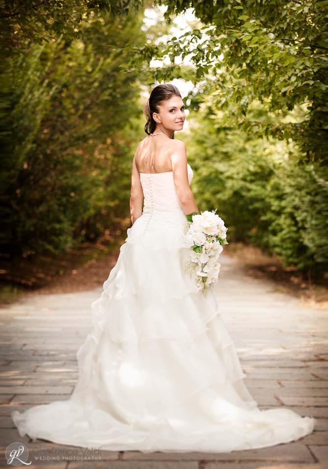 foto della sposa in un tunnel di alberi verdi a torino