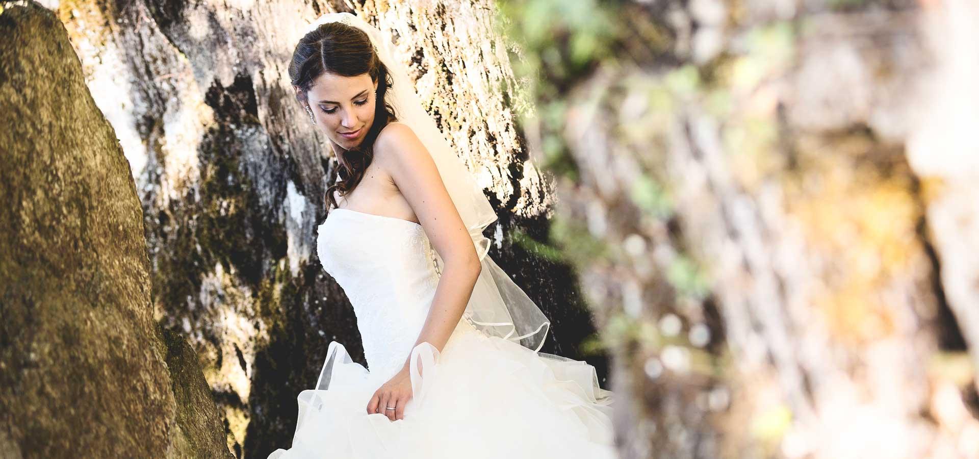 la sposa si arrampica tra le rocce dopo il matrimonio per scattare una foto d'impatto