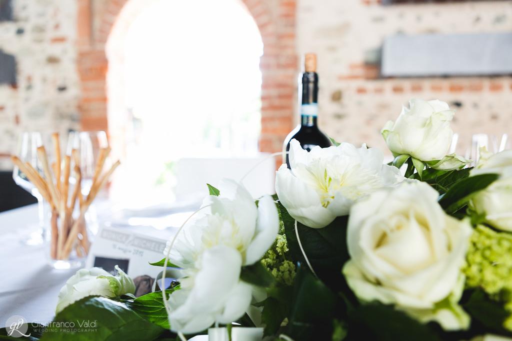 Il tavolo degli sposi abbellito da una composizione di rose bianche