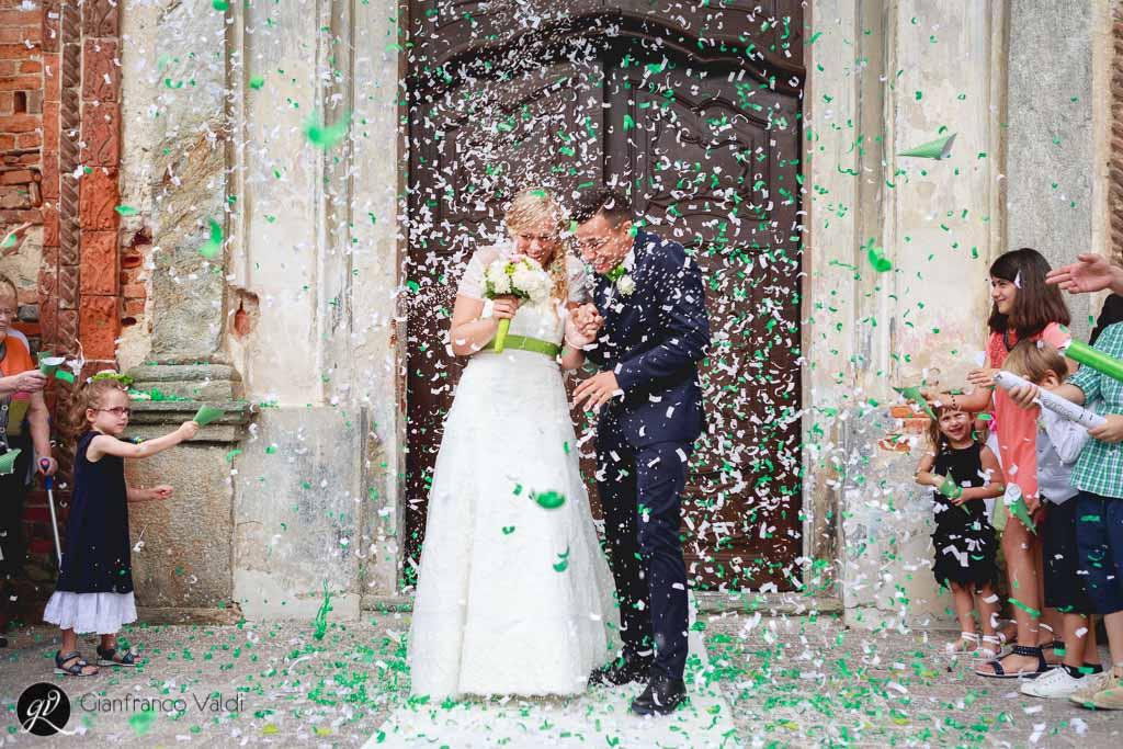 i novelli sposi sotto una cascata di coriandoli colorati