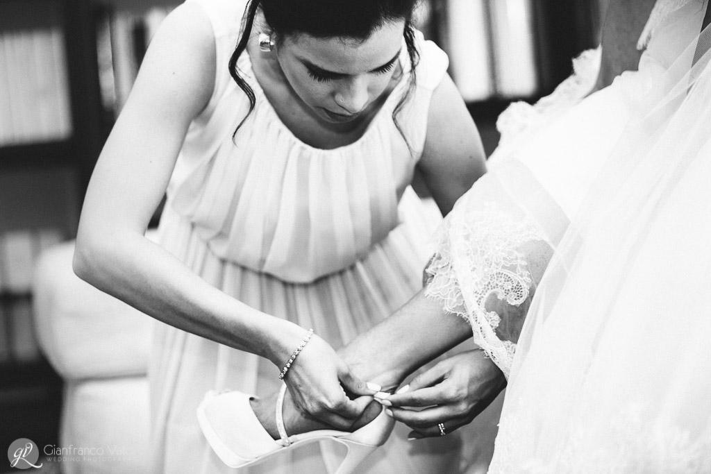 la testimone aiuta la sposa a chiudere le scarpe
