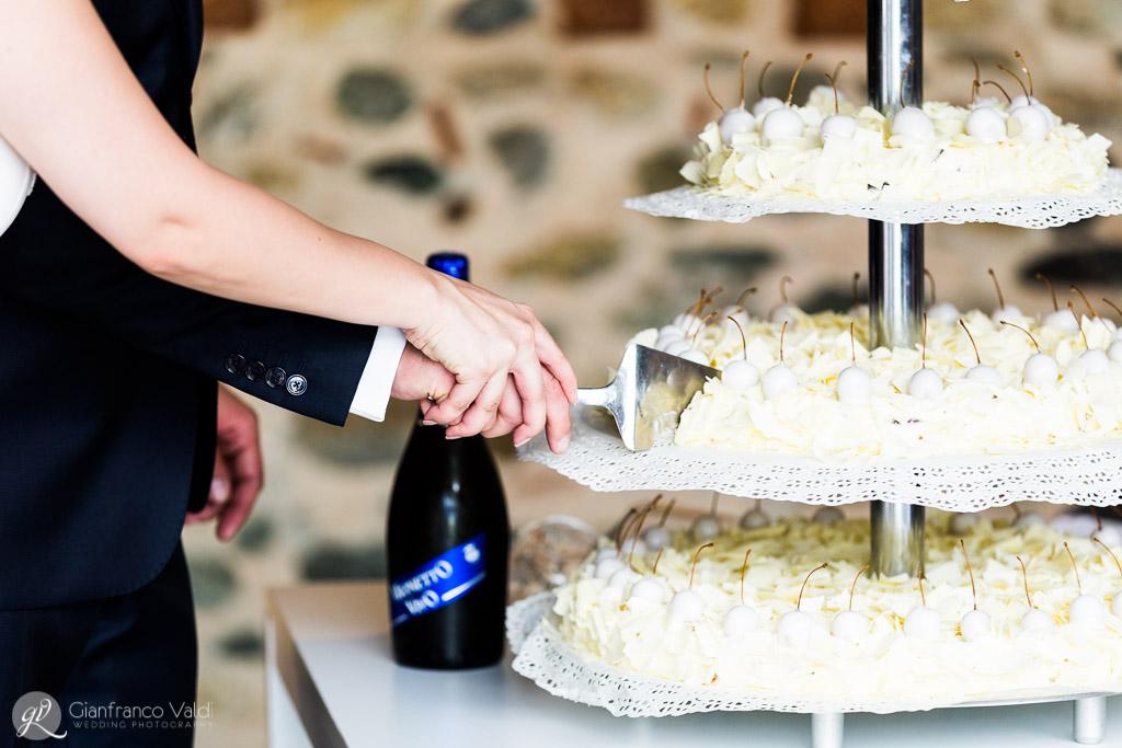 Primo piano delle mani che tagliano la torta